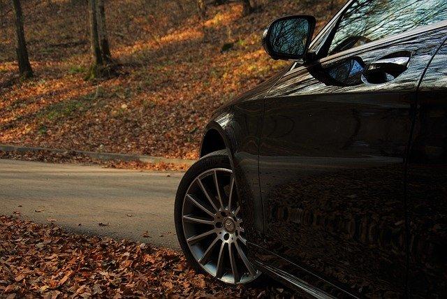 Avant de voiture Mercedes sur une route de forêt en automne.